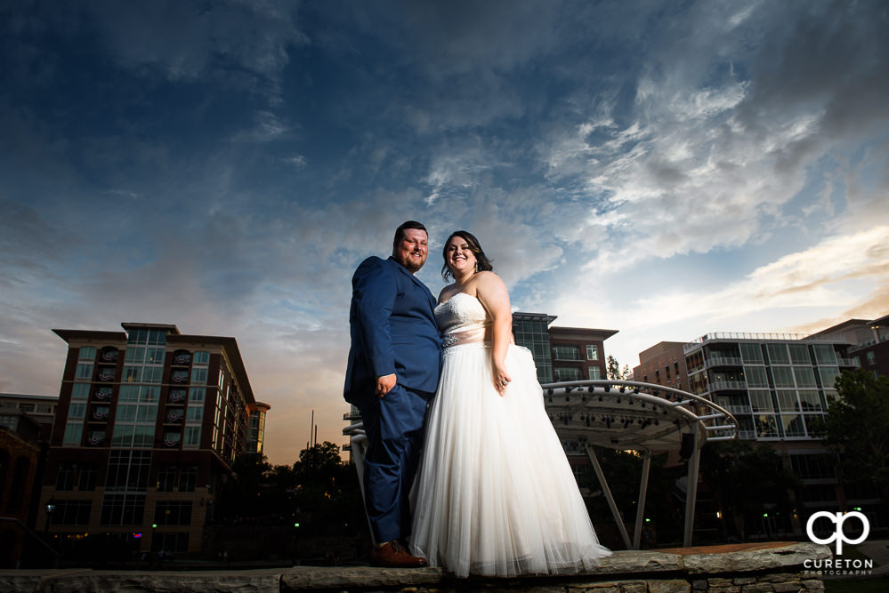 Bride and groom at sunset with an epic sky backdrop in downtown Greenville SC.