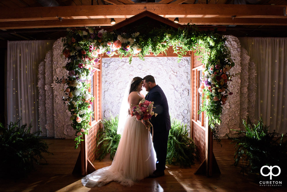 Bride and groom with a custom floral arbor at their Huguenot Loft wedding in Greenville SC.