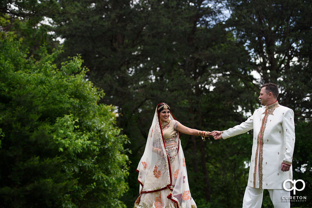 Bride leading groom after their Indian wedding at Embassy Suites in Greenville,SC.