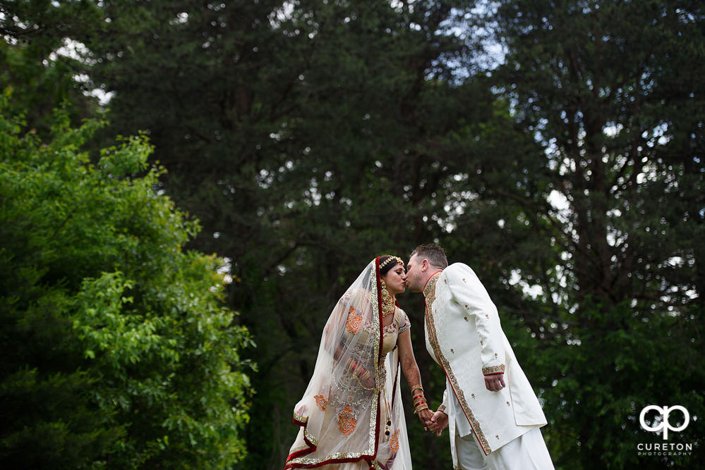 Groom kissing his bride after their Indian wedding at Embassy Suites in Greenville,SC.