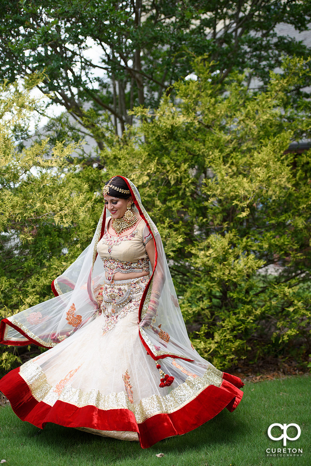 Indian bride twirling in her dress.