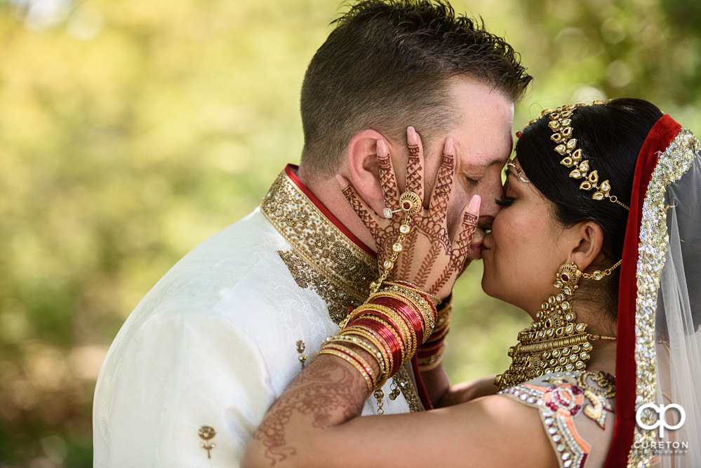 Bride kissing her groom after the ceremony at their Indian wedding at Embassy Suites in Greenville,SC.