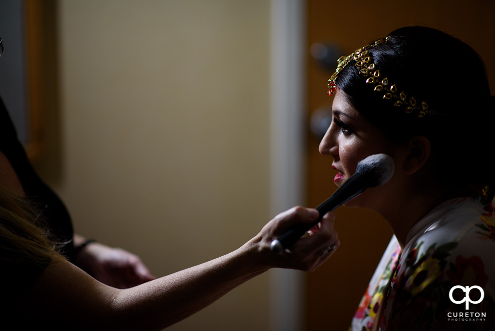 Indian bride getting makeup by Cotton Rouge.