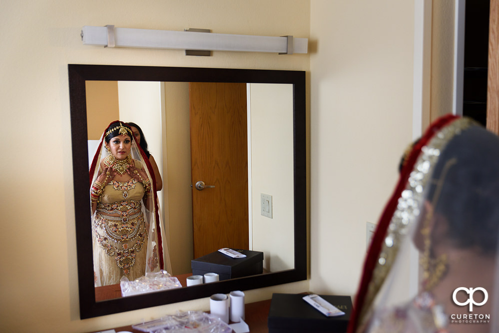 Indian bride getting ready for her wedding looking in the mirror.