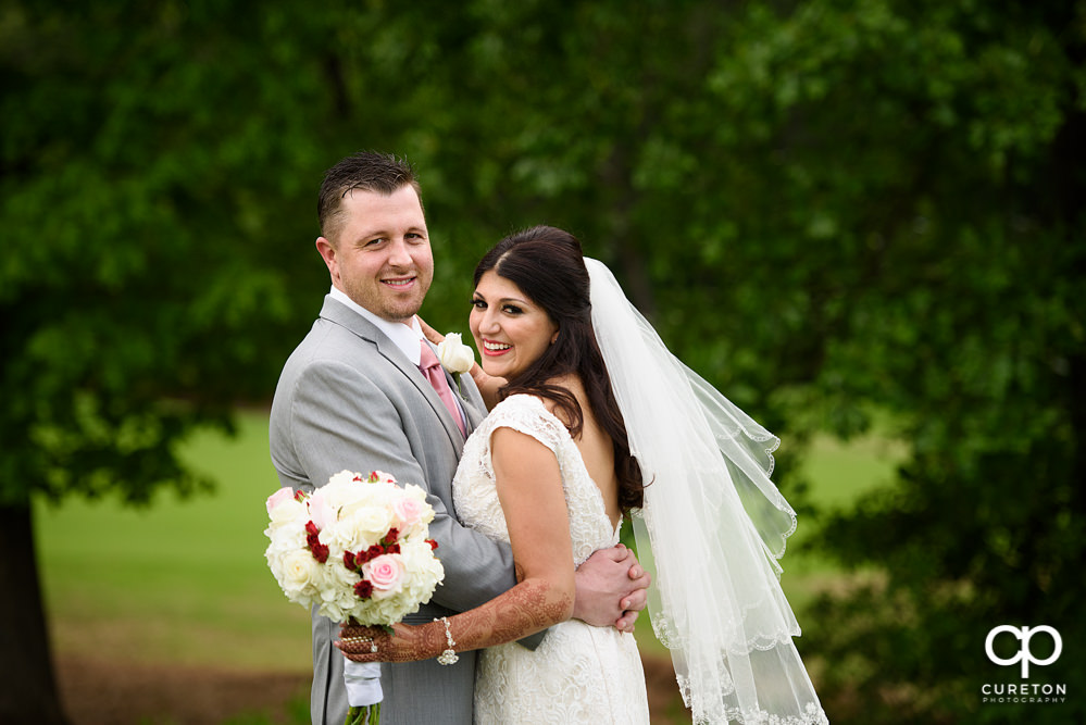 Bride and groom on the golf course at Embassy Suites.