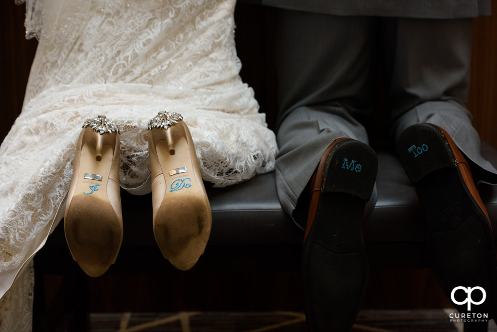 Bride and groom's shoes with words on them.