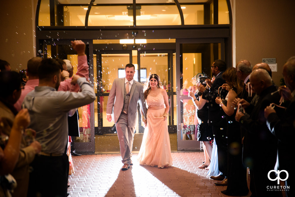 Bride and groom grand exit though bubbles at Embassy Suites.