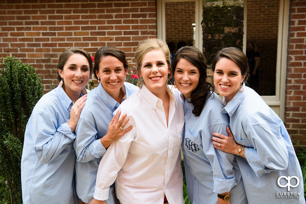 Bride and bridesmaids in monogrammed shirts.
