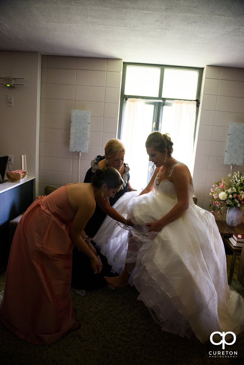 Bridesmaids helping the bride into her shoes.