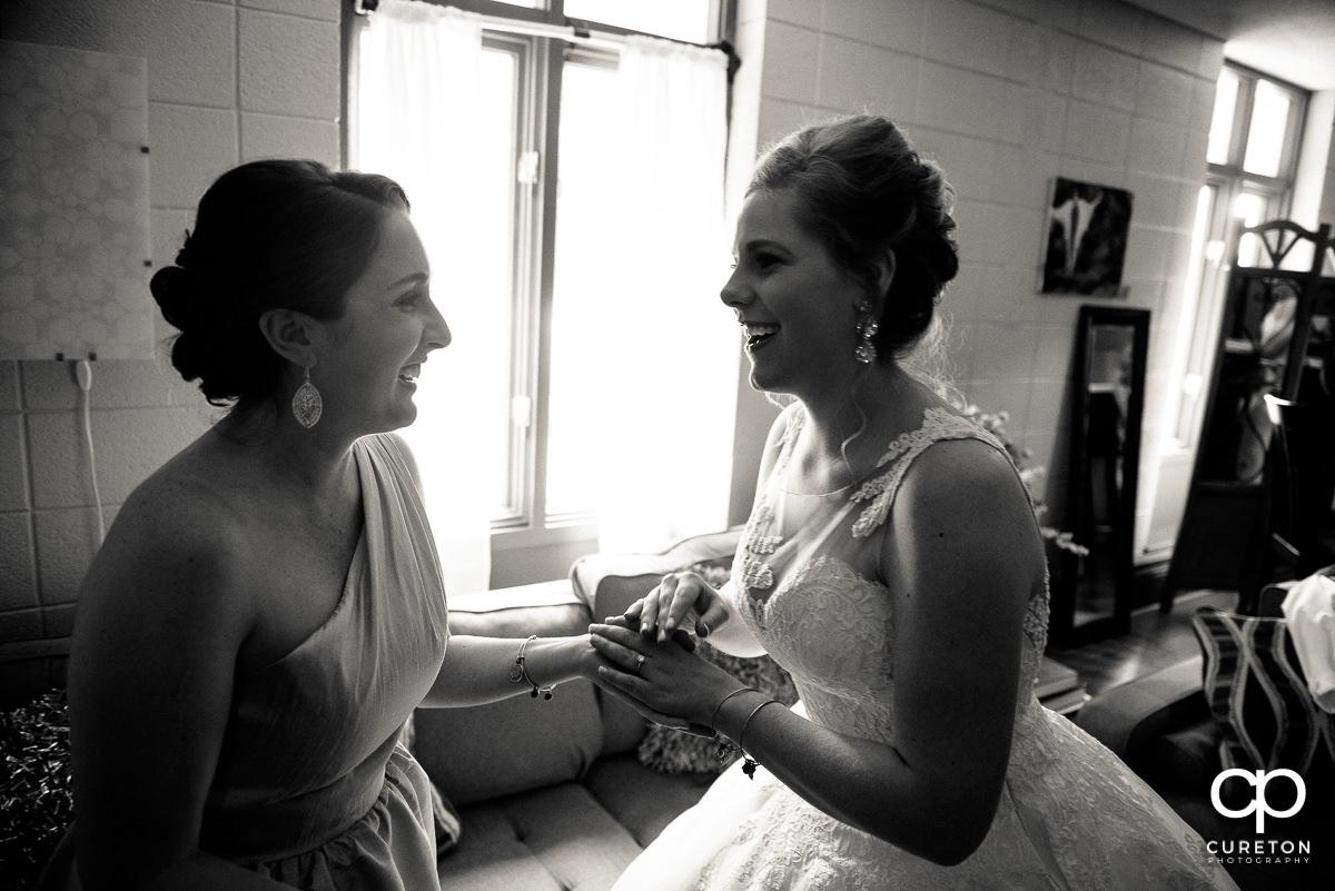 Bride and bridesmaid laughing.