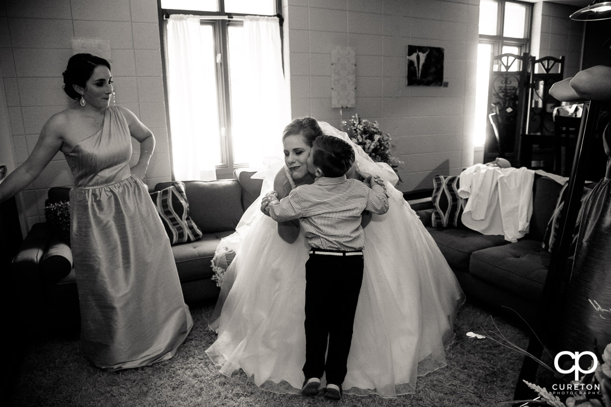 Bride getting kissed on the cheek by a little boy.