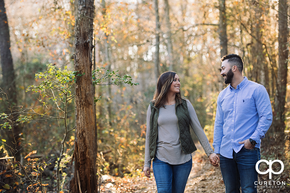 Future bride and groom walking down a trail during their Lake Conestee Nature Park engagement session.
