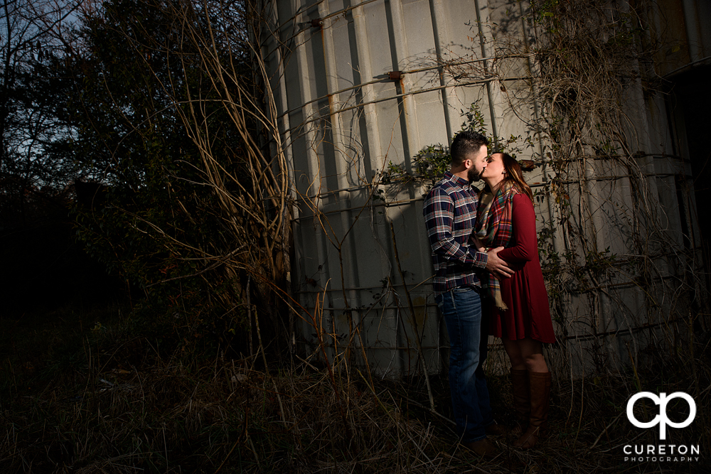 Engaged couple kissing while leaning on a corn silo.
