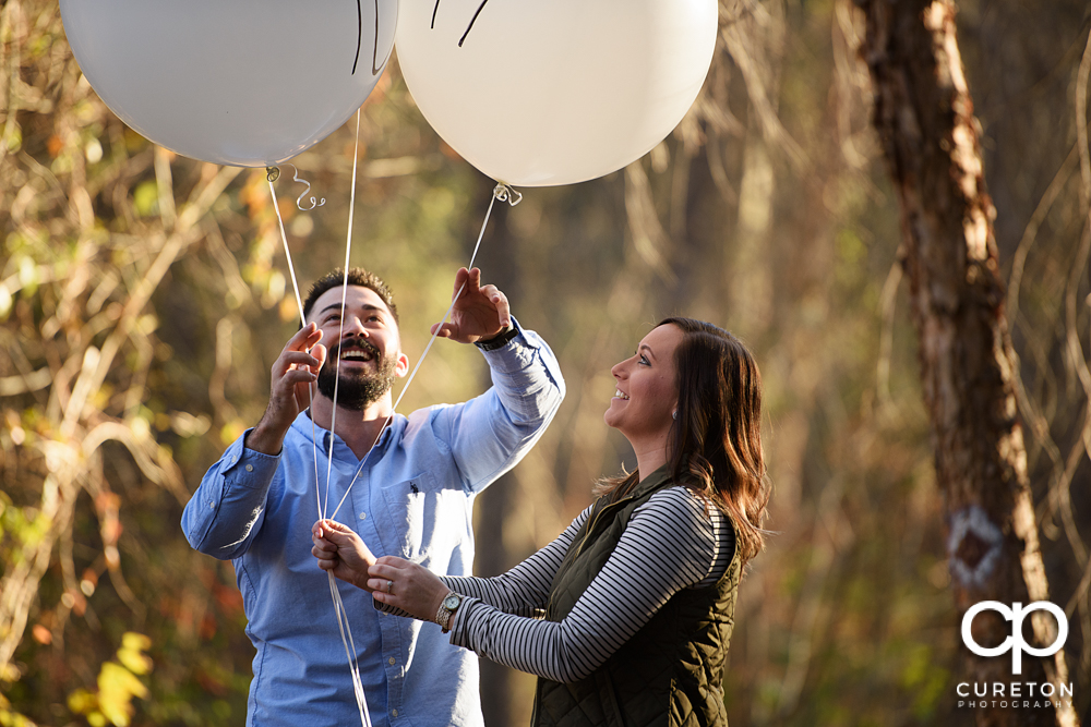 Engaged couple with balloons.