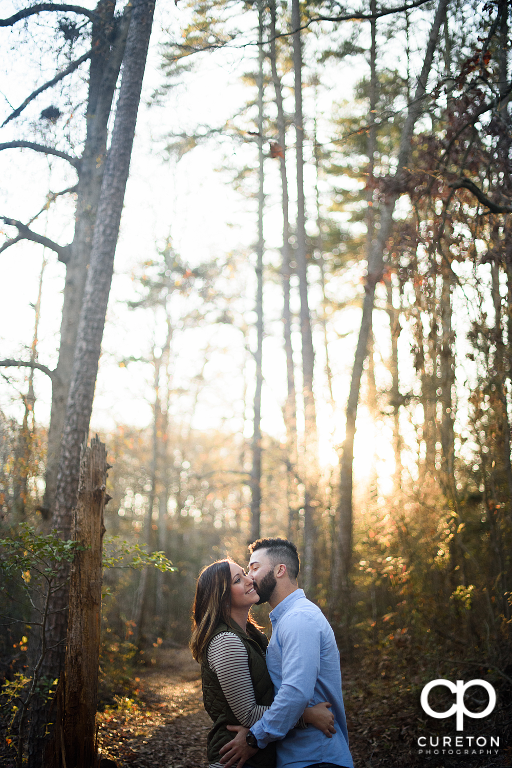 Man kissing his faincee on the cheek during their Lake Conestee Nature Park engagement session..