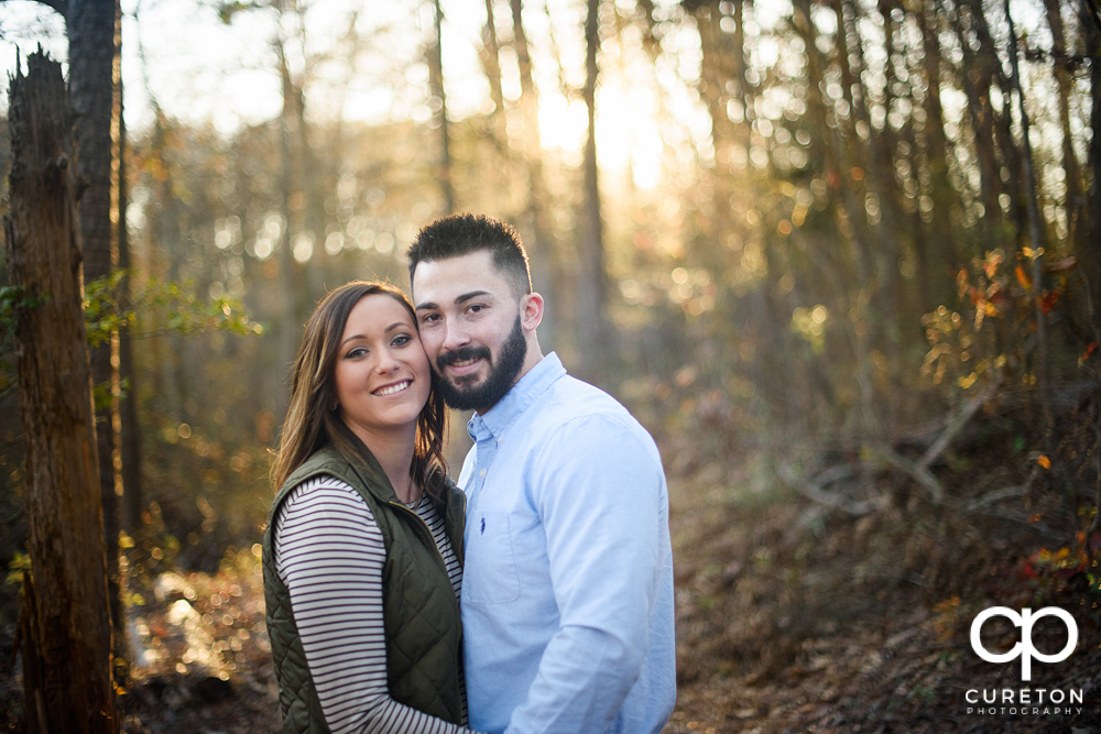 Engaged couple on a trail backlit by the sun.