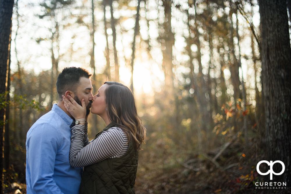 Future bride and groom kissing in the forest during their engagement session in Greenville,SC.