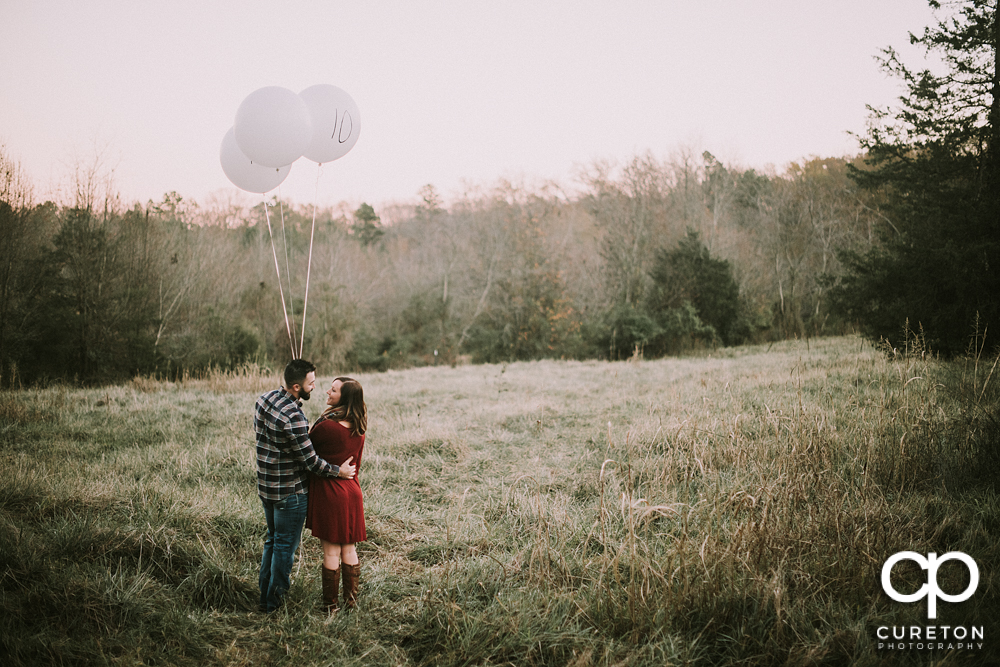 Bride and groom in a field with balloons in Greenville,SC.