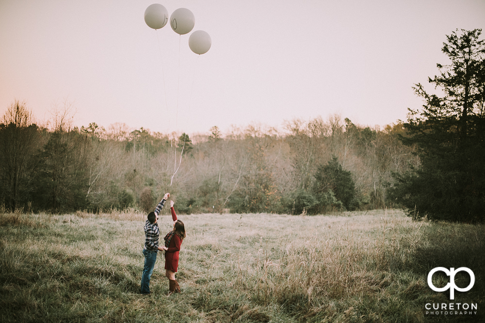 Engaged couple letting of of balloons.