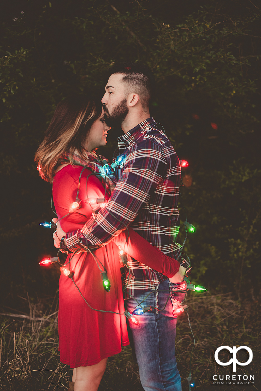 Engaged couple covered in Christmas lights.