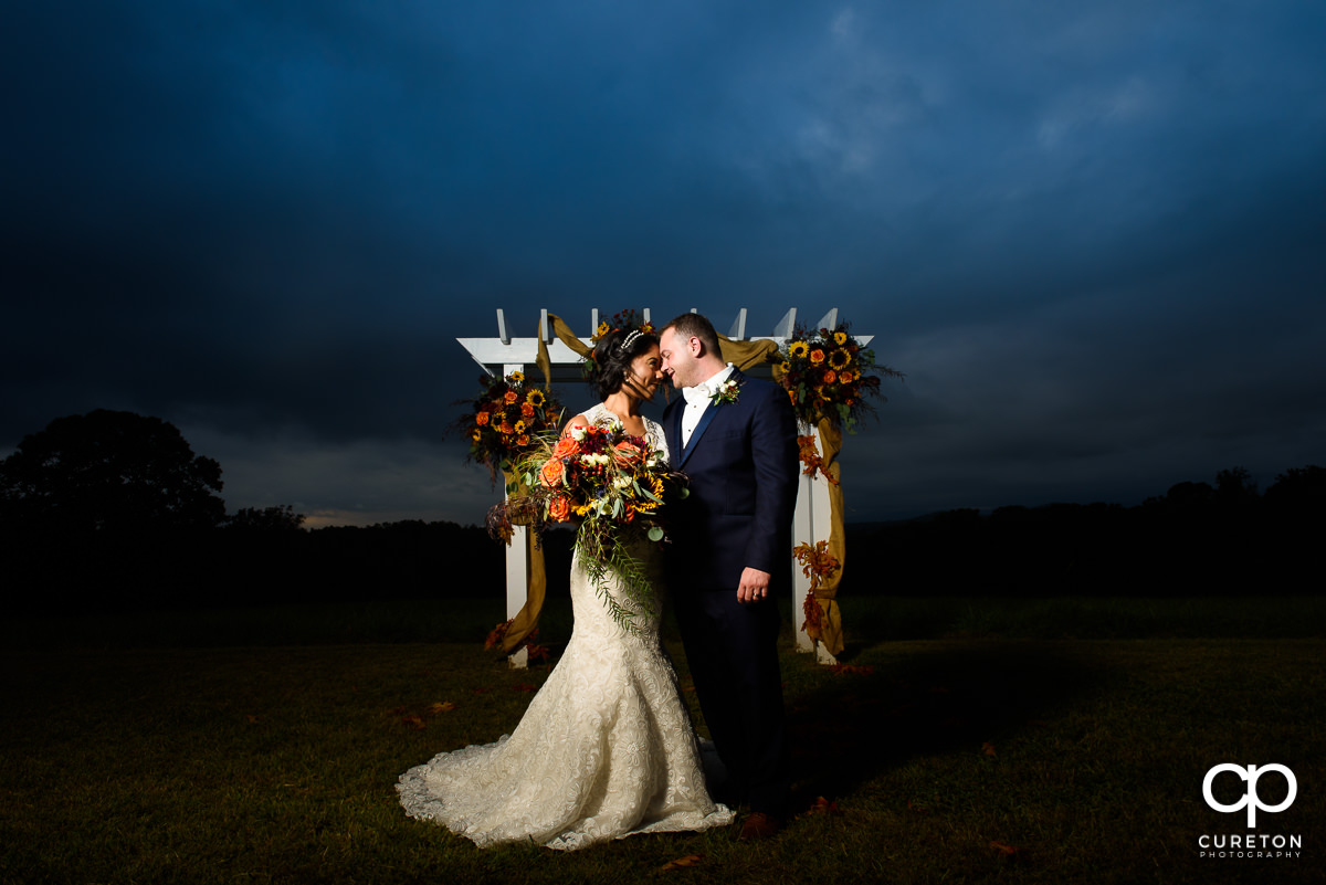 Bride and groom standing in the field after their fall wedding at Lindsey Plantation in Taylors,SC.