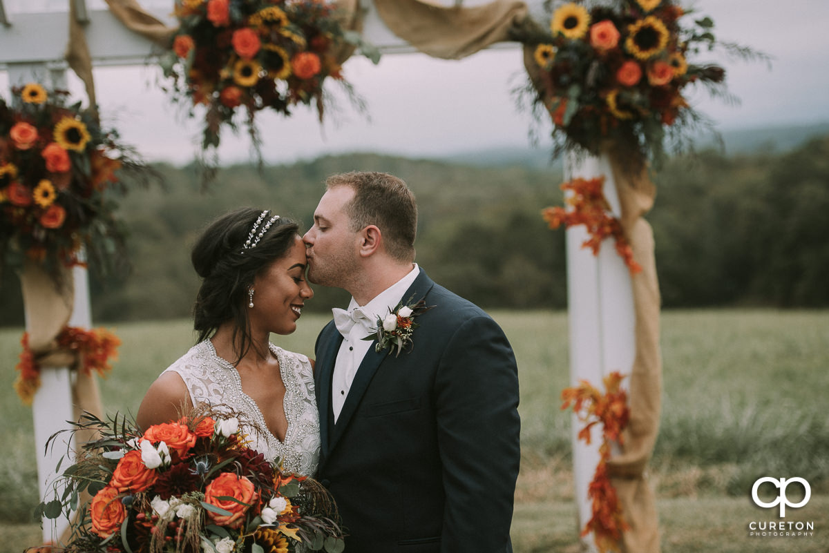 Groom kissing his bride on the forehead with beautiful fall flowers in the background at their Lindsey Plantation wedding.