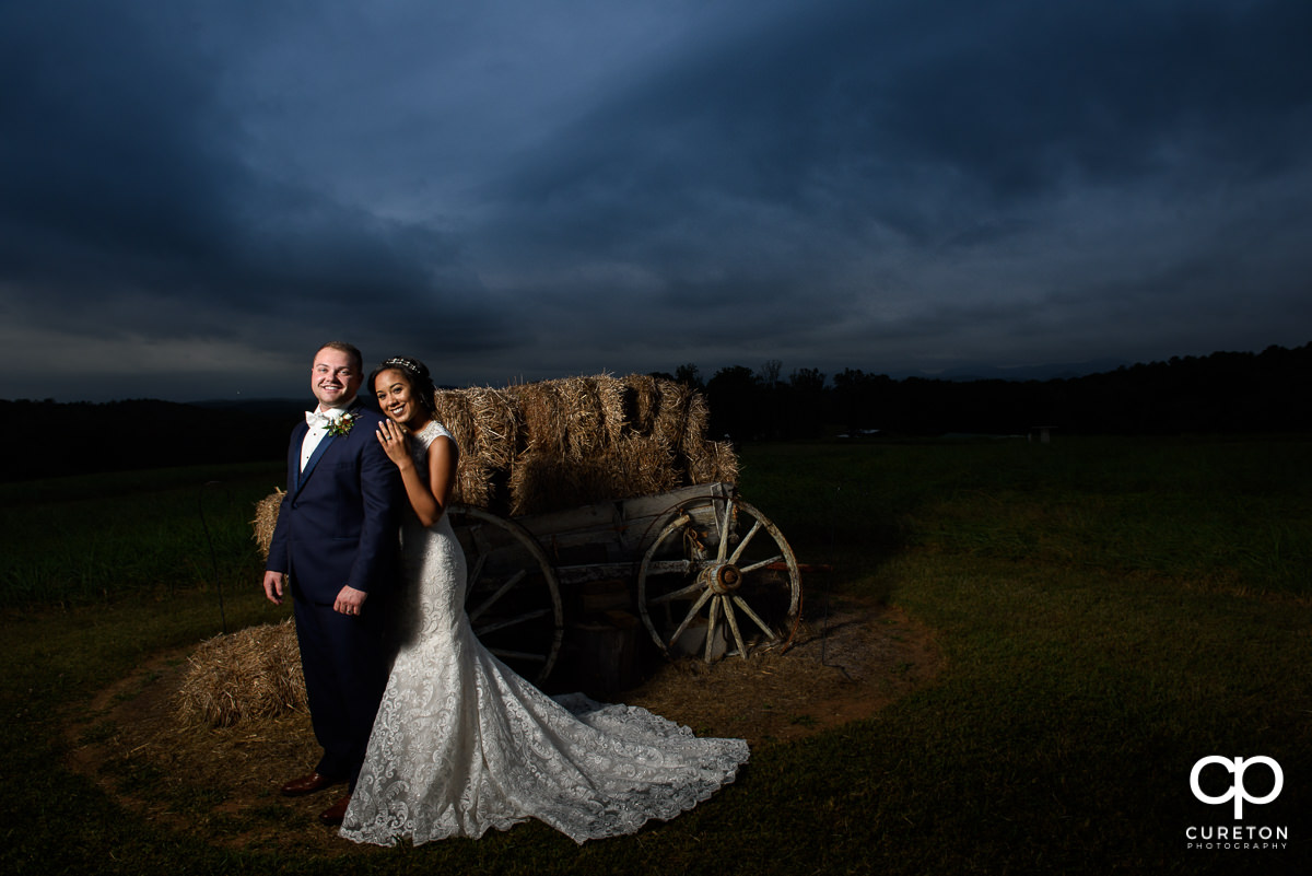 Bride and groom posing by the wagon in the field at Lindsey Plantation.