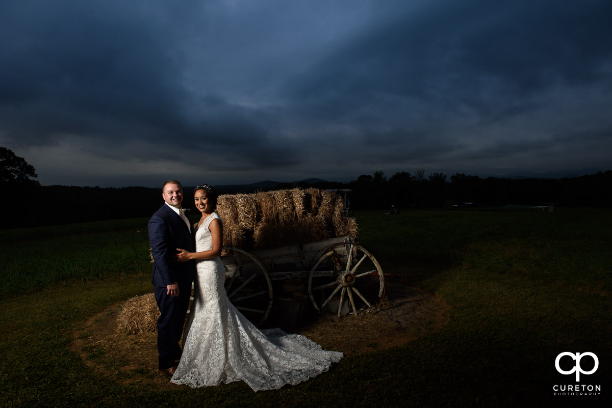 Groom and bride by a wagon at Lindsey Plantation at sunset after their fall wedding.