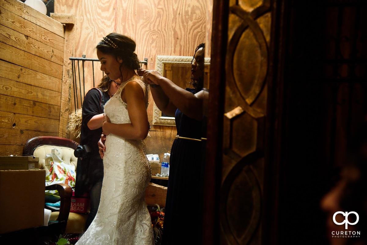 Bride putting on her dress at Lindsey Plantation.