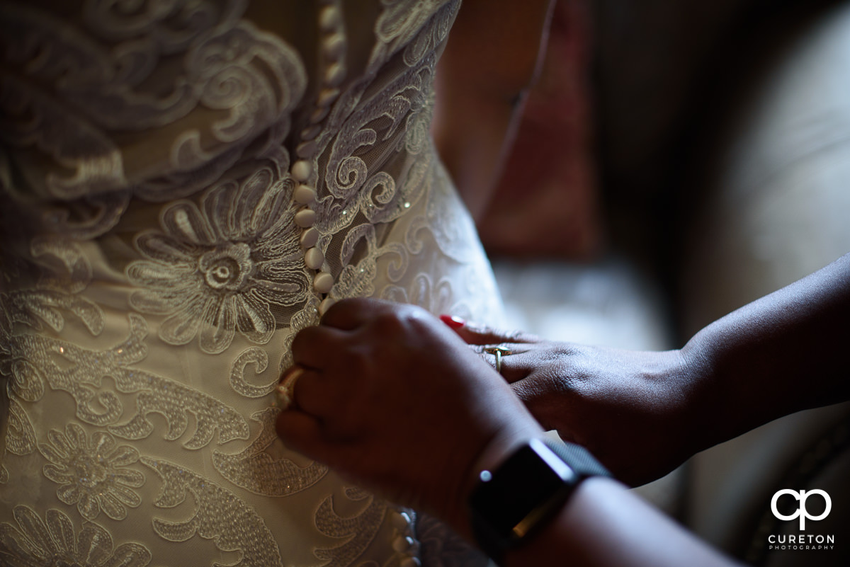 Bride's mom's hands on the back of her dress.