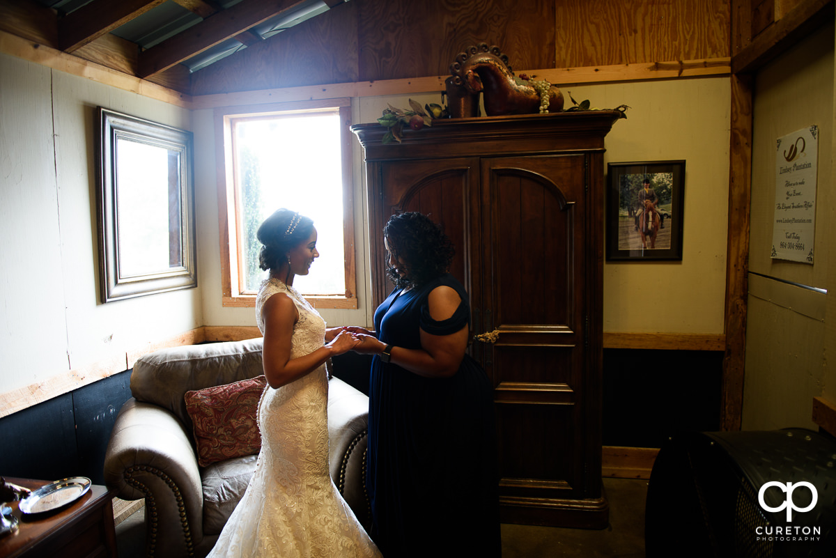Bride and her mother in front of a window.