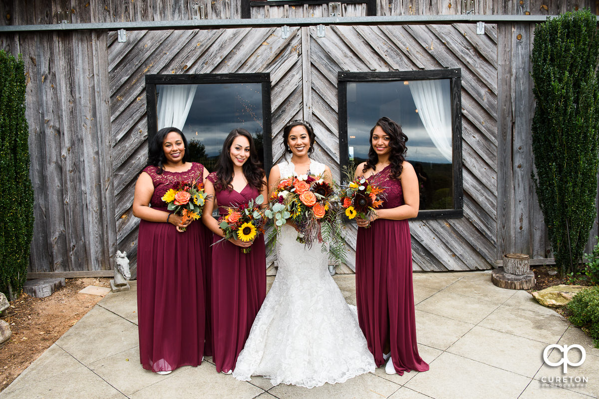 Bride and bridesmaids in front of the barn at Lindsey Plantation in Taylors,SC.