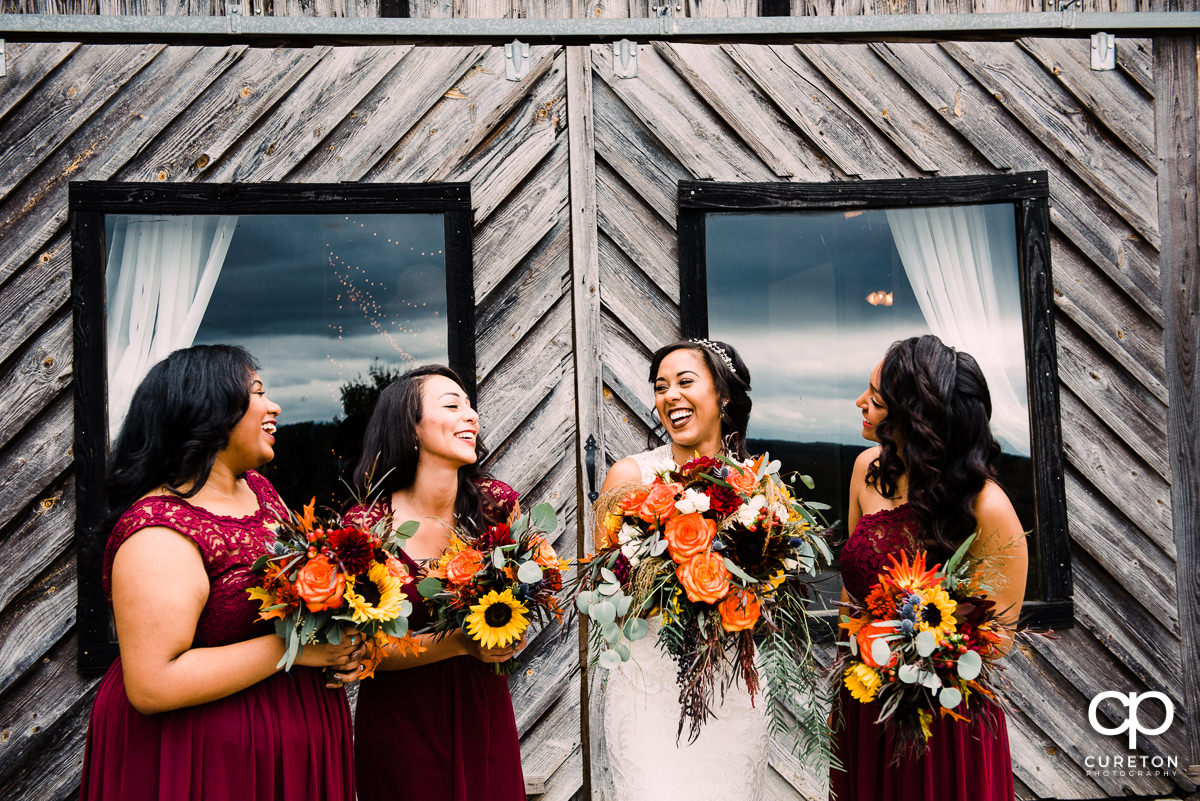 Bride laughing with her bridesmaids before the wedding.