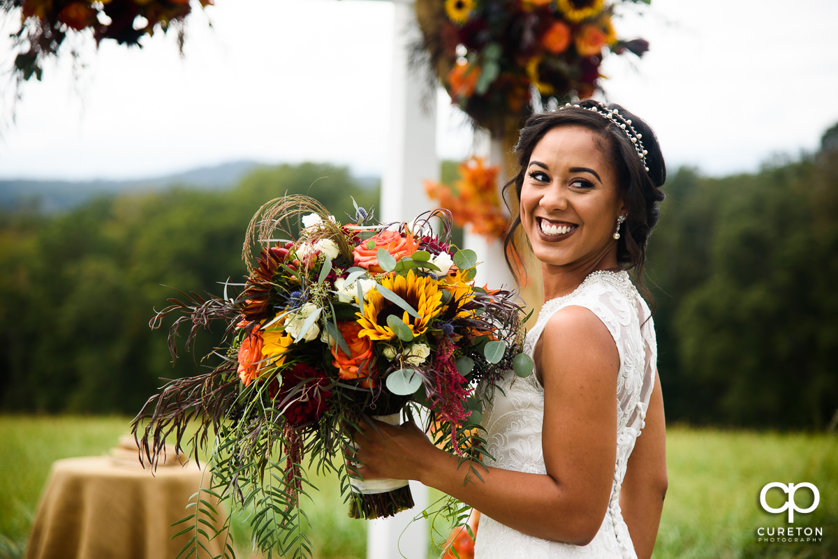 Bride smiling with her fall florals.
