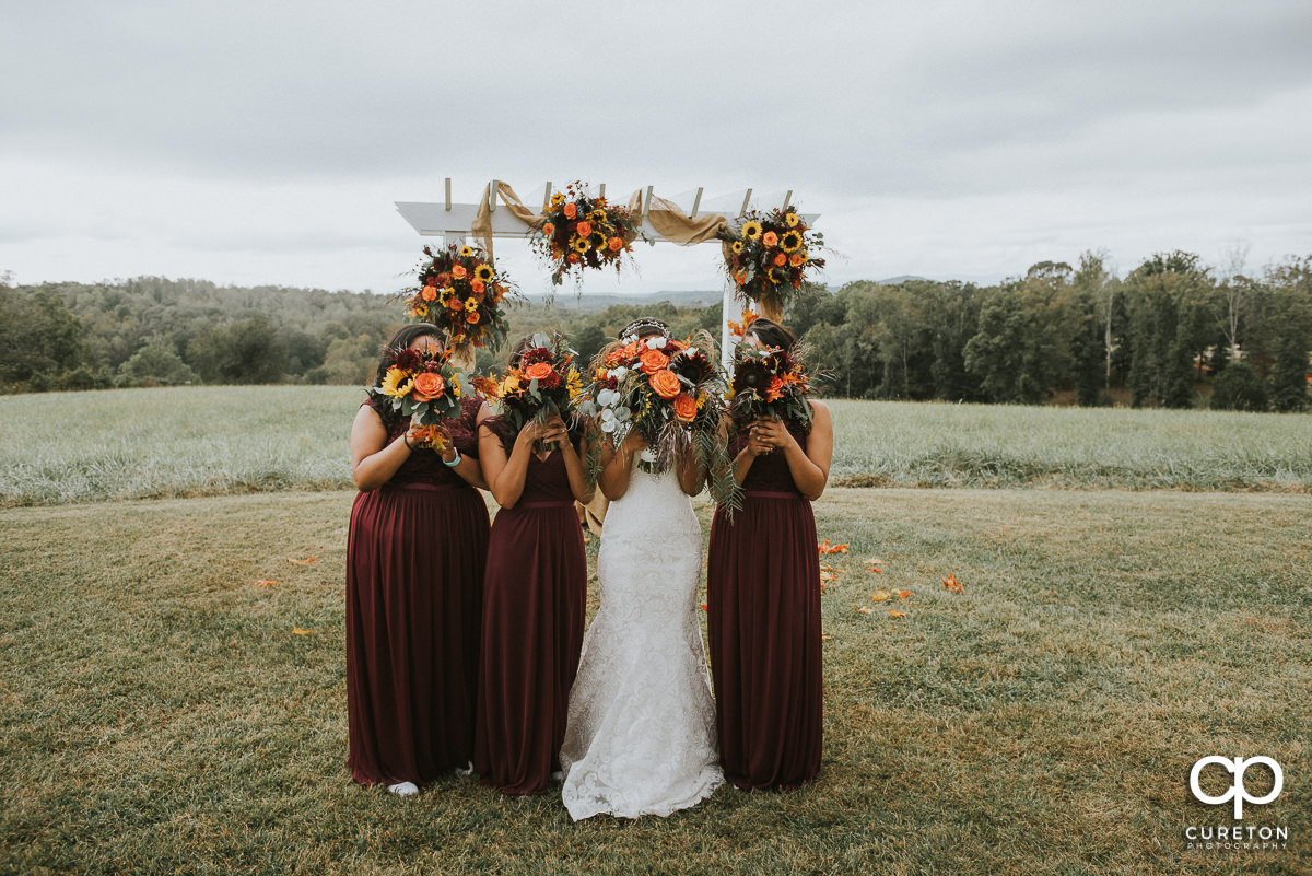 Bridesmaids holding fall bouquets in front of their faces before the wedding.