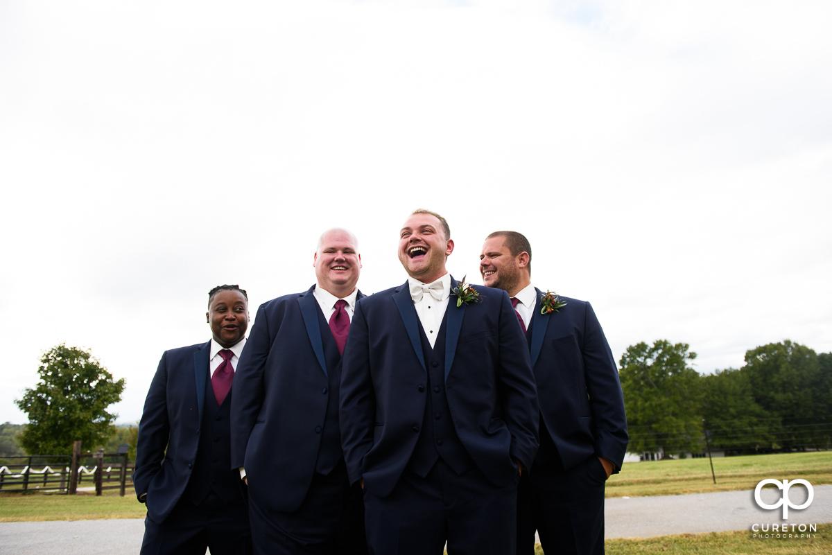Groom laughing with groomsmen.