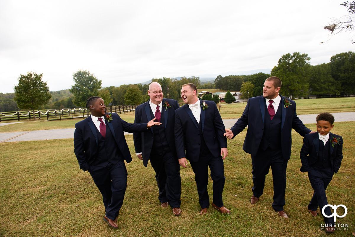 Groomsmen walking in the field.