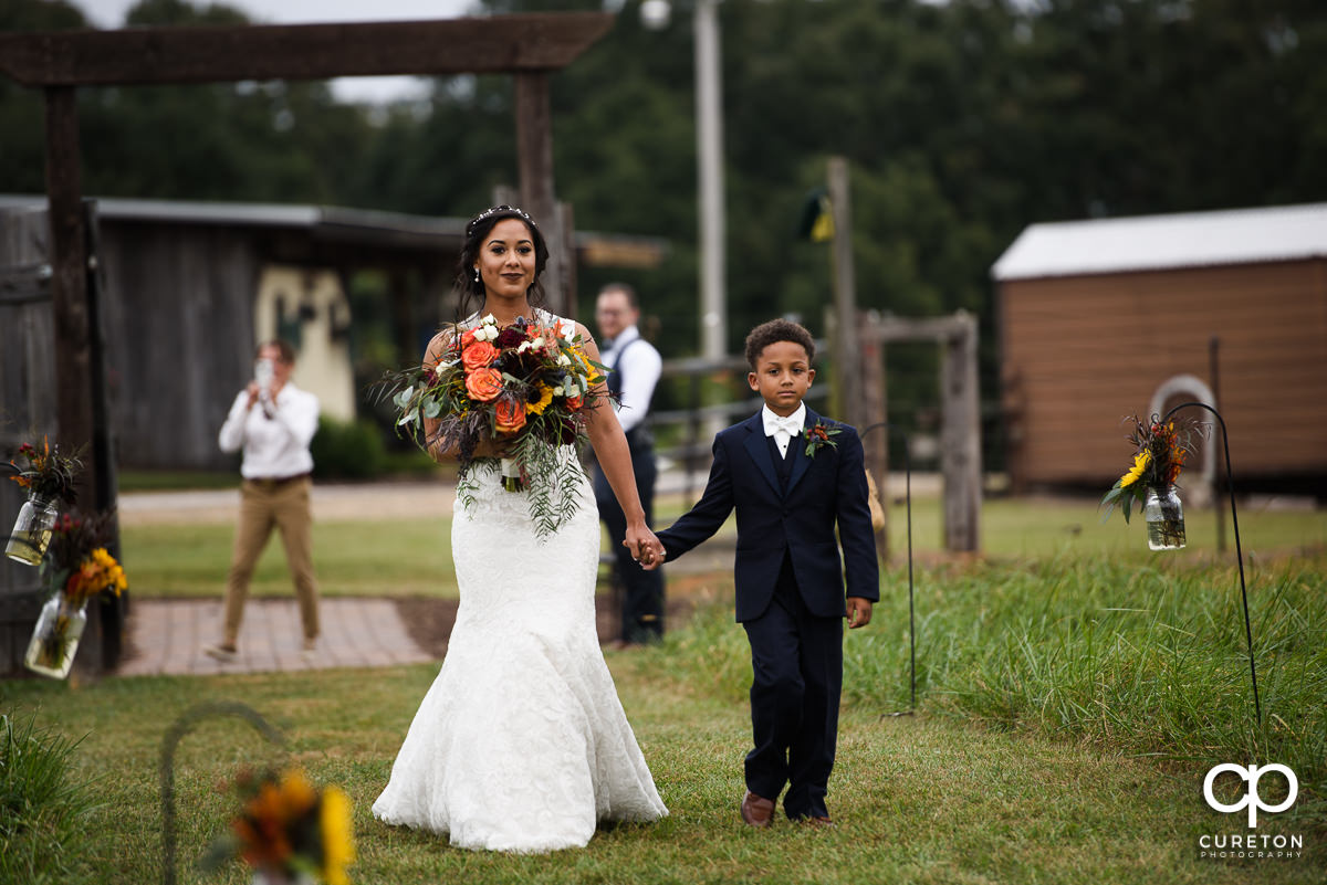 Bride and her son walk down the aisle at her wedding at at Lindsey Plantation in Taylors,SC.