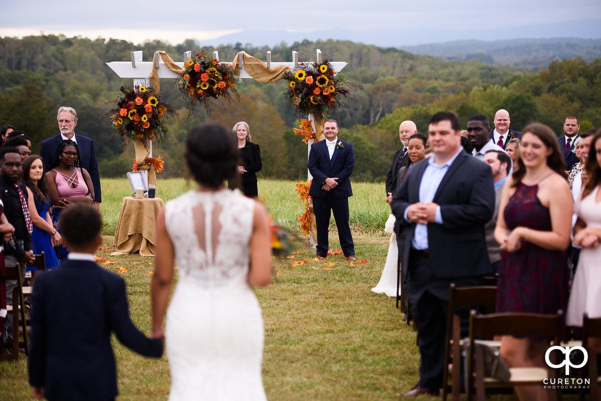 Groom sees his bride walking down the aisle.