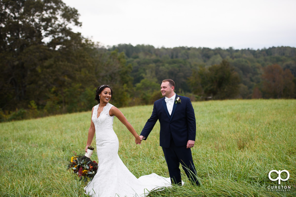 Bride and groom walking in a field at Lindsey Plantation.
