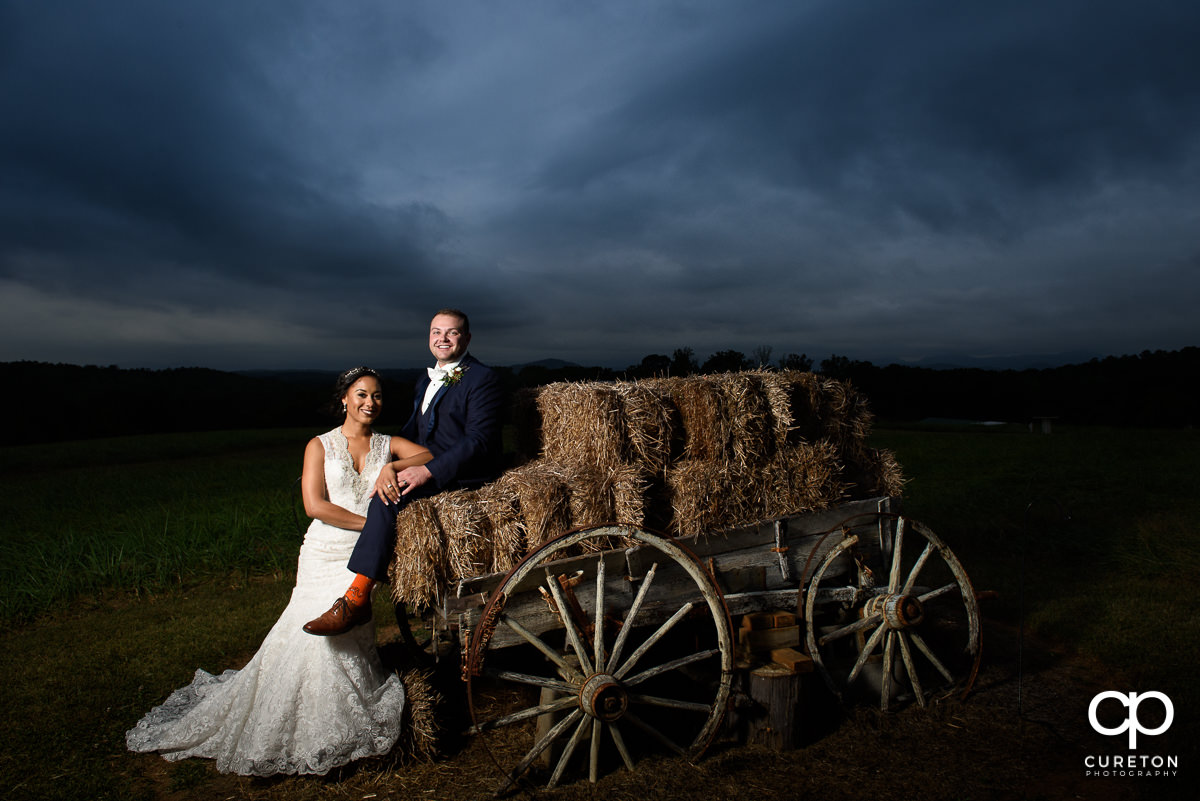 Bride and groom standing by an antique wagon.