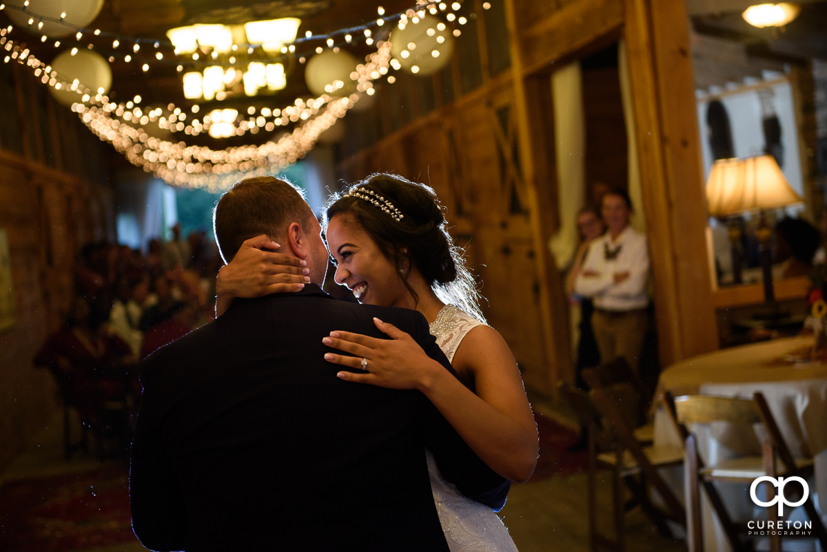 Bride smiling during her first dance with her husband.