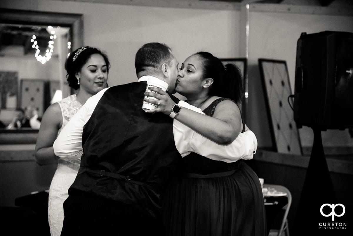 Bridesmaids hugging the groom.