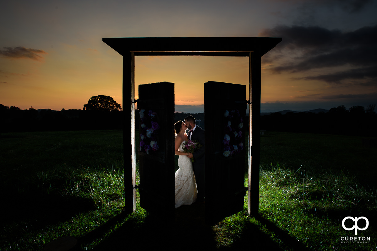 Bride and groom kissing at sunset in the field at Lindsey Plantation.