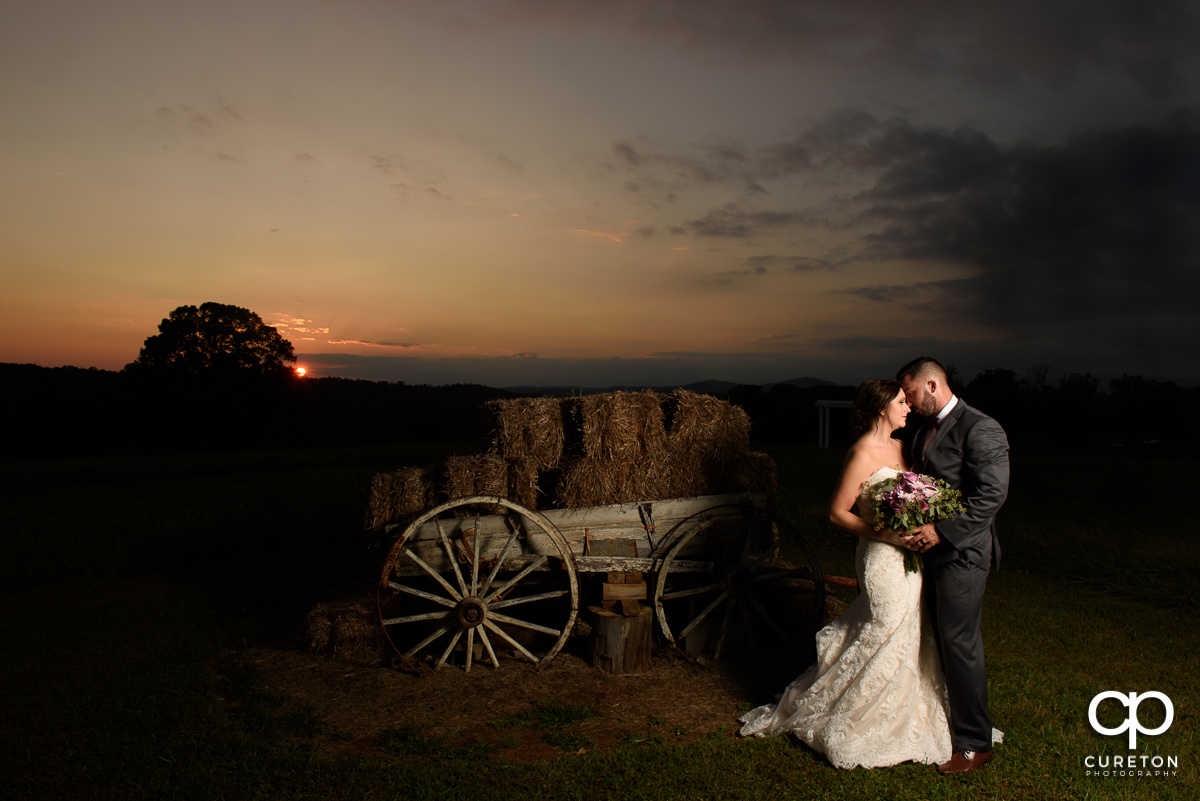 Bride and groom near the antique wagon in the field at Lindsey Plantation.