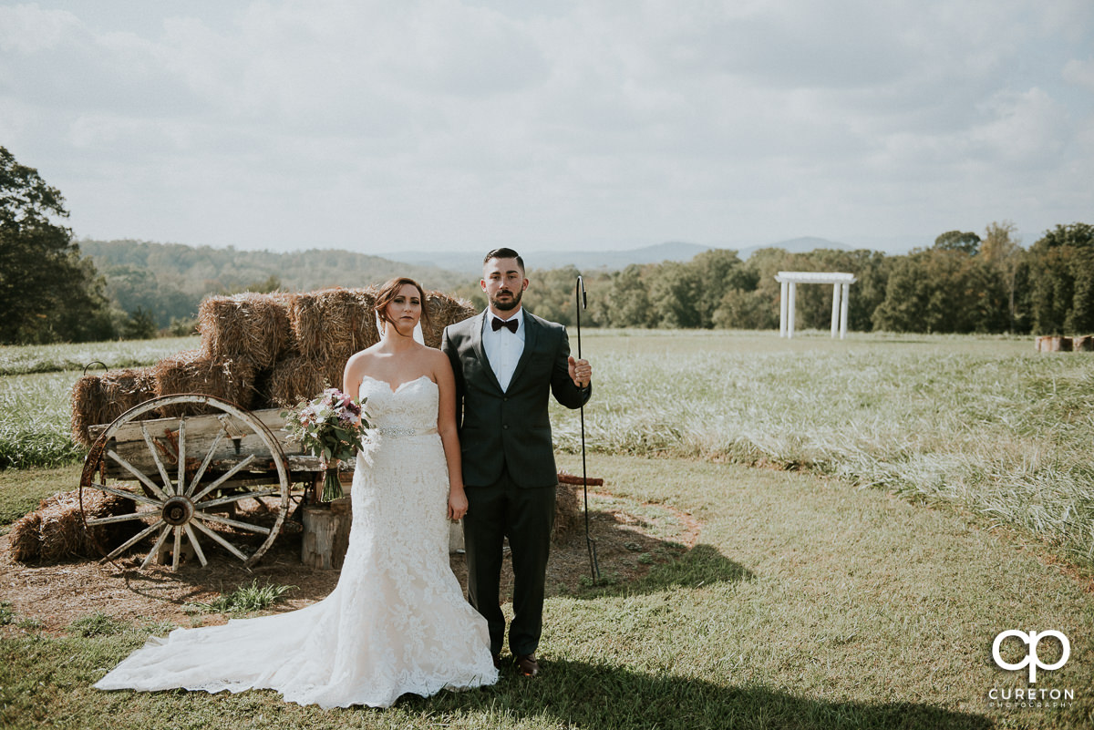 Bride and groom in the field at Lindsey Plantation reproducing the American Gothic pose.