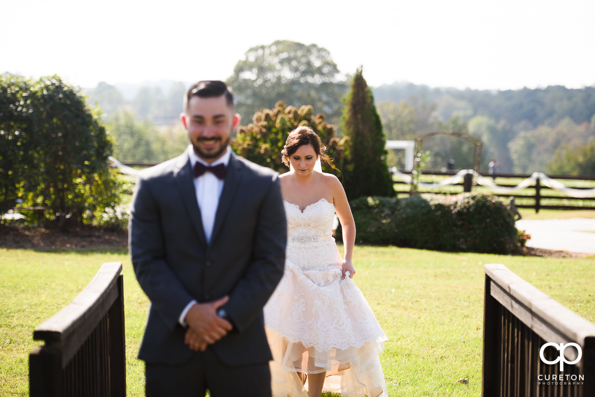 Bride walking behind her groom at the first look.