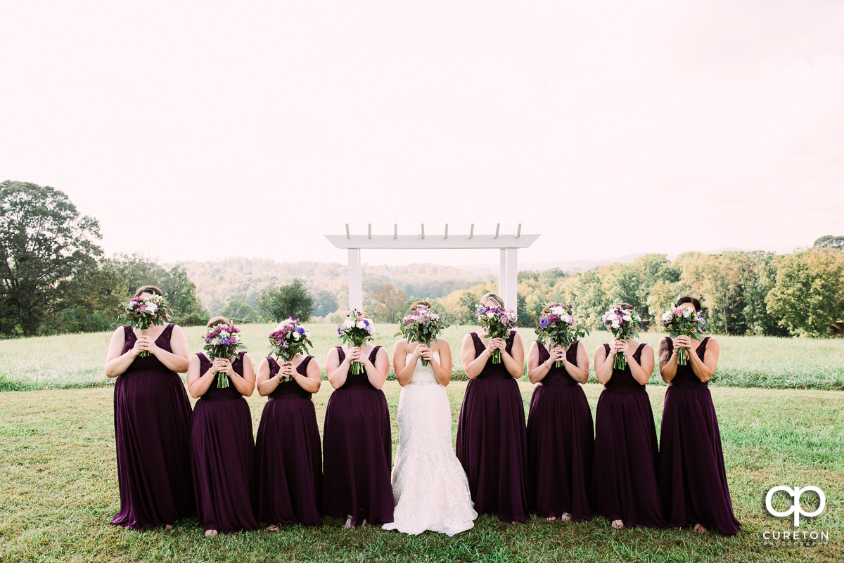 Bridesmaids holding flowers up to their faces.