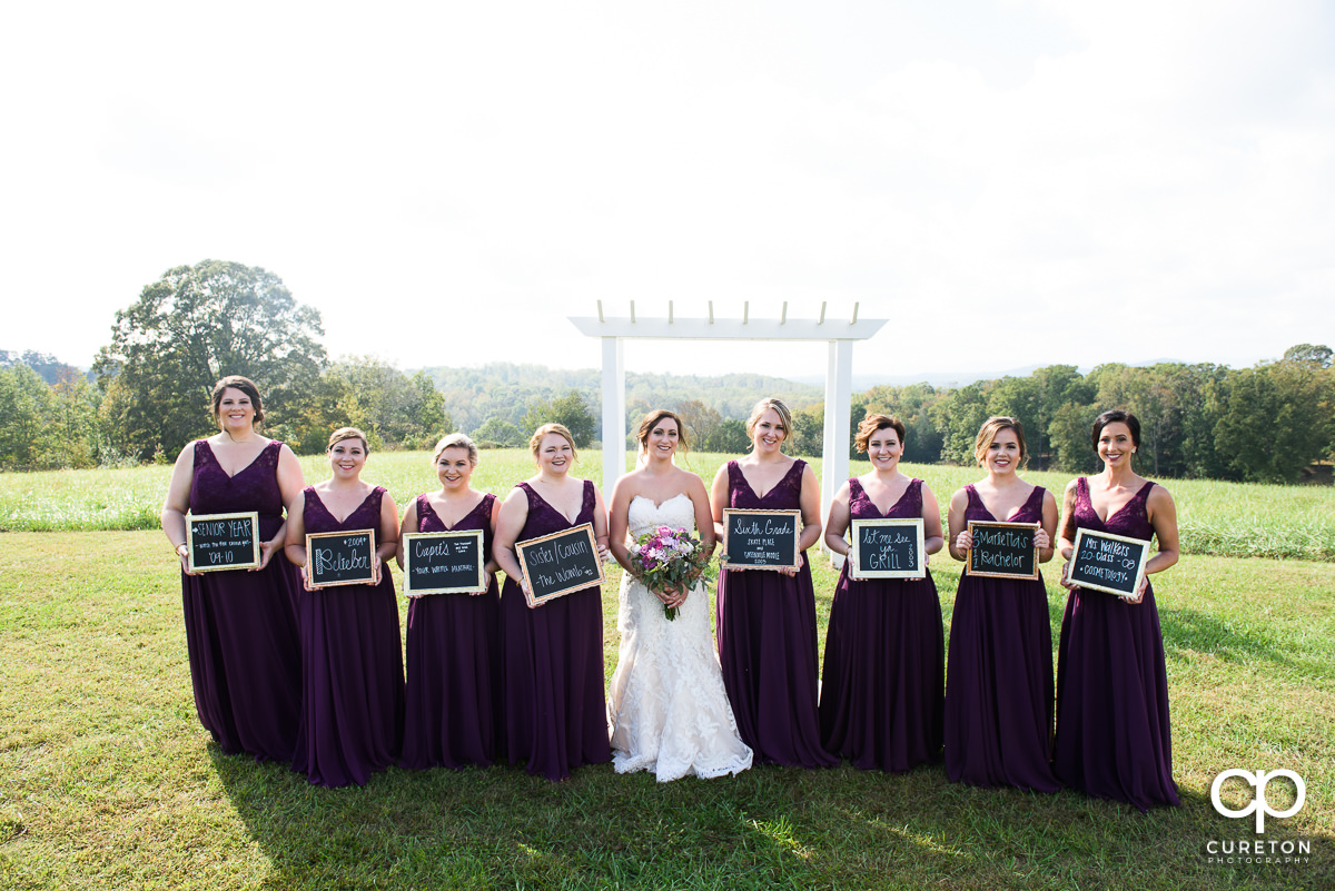 Bridesmaids holding signs how they met the bride.