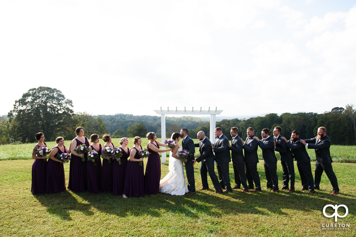 Wedding party pushing the bride and groom together before the ceremony at Lindsey Plantation.